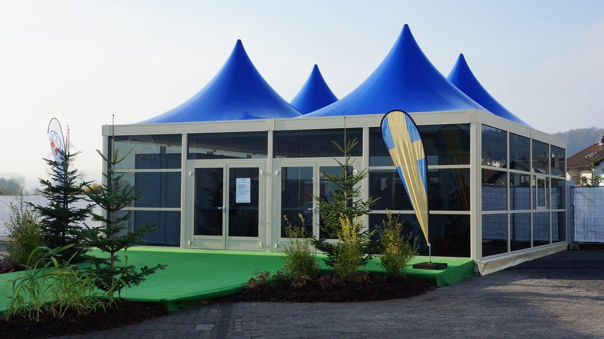 Hala namiotowa ze szklanymi ścianami, podwójnym wejściem i niebieskimi dachami w stylu pagoda