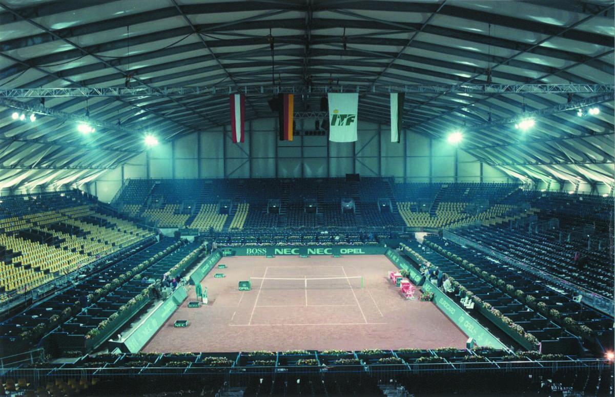 Duża hala namiotowa zaadoptowana na kort do tenisa ziemnego oraz trybuny