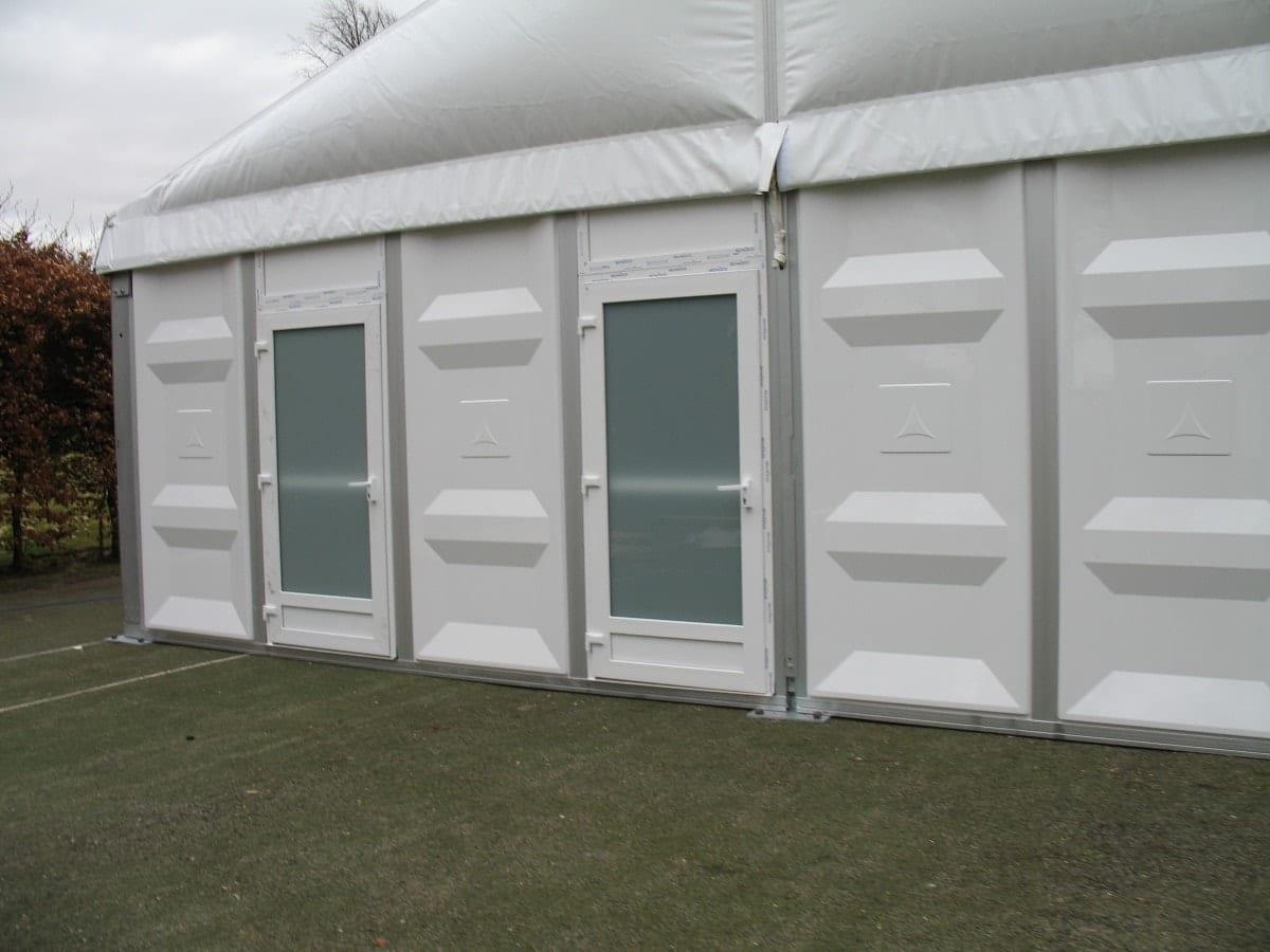 Namiot z parą plastikowych drzwi i skośnym dachem
